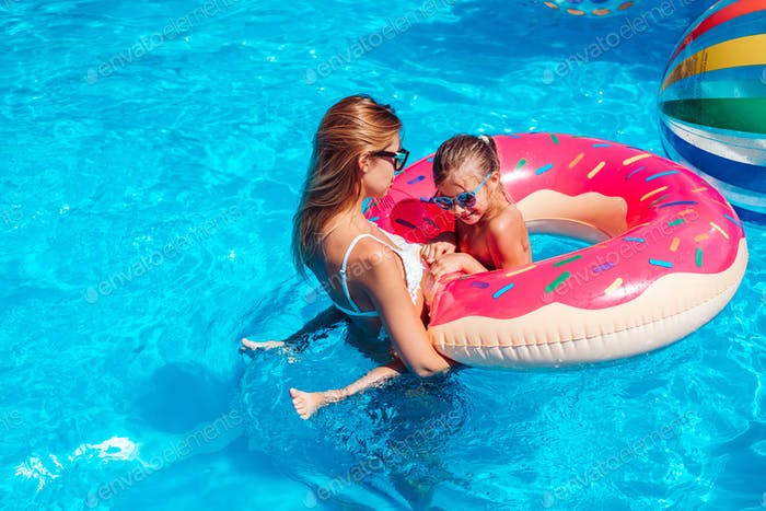 Little girl with her mom in swimming pool.
