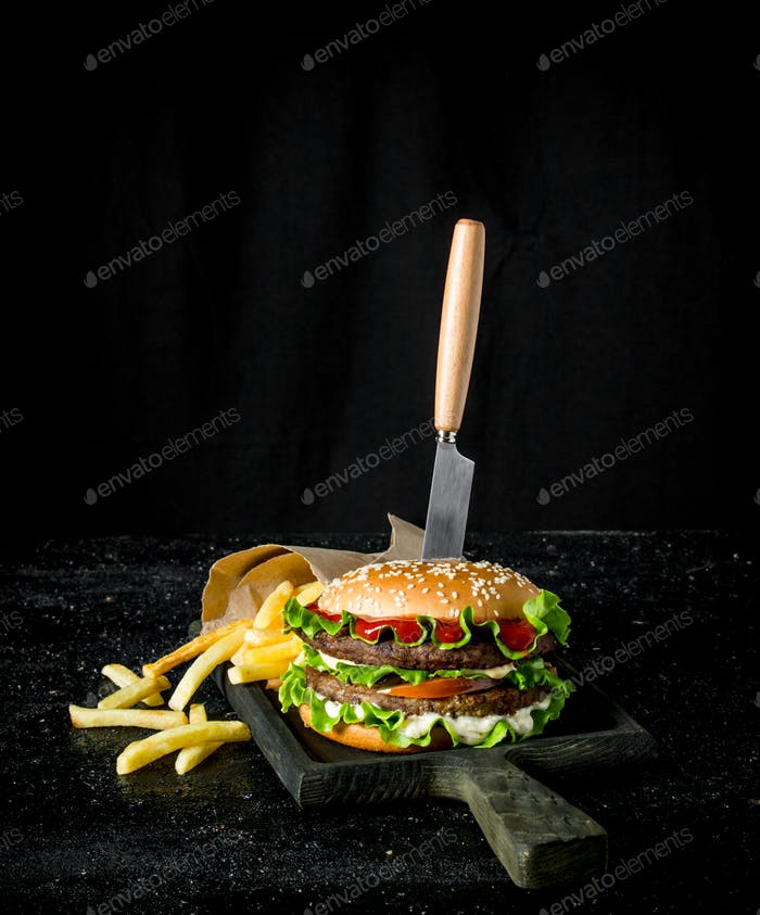 Burger with a knife and fries.