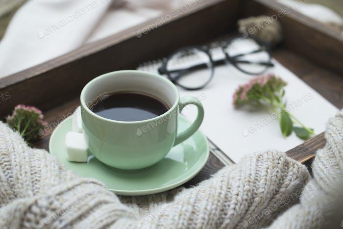 Notizblock und eine Tasse Kaffee auf einem Tablett