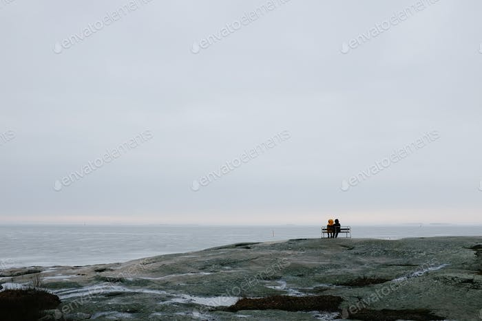 Two people sitting on a chair by the sea during winter