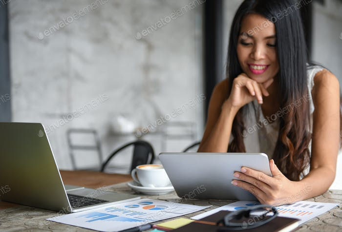 Asia female businessmen are using the tablet during leisure. She smiles happy.