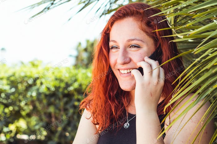 Close up of smiling attractive girl with redhead talking on mobile phone while standing outdoors