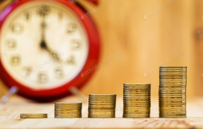 Business success - alarm clock and money coins