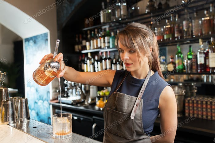 barmaid with glass and jug preparing cocktail