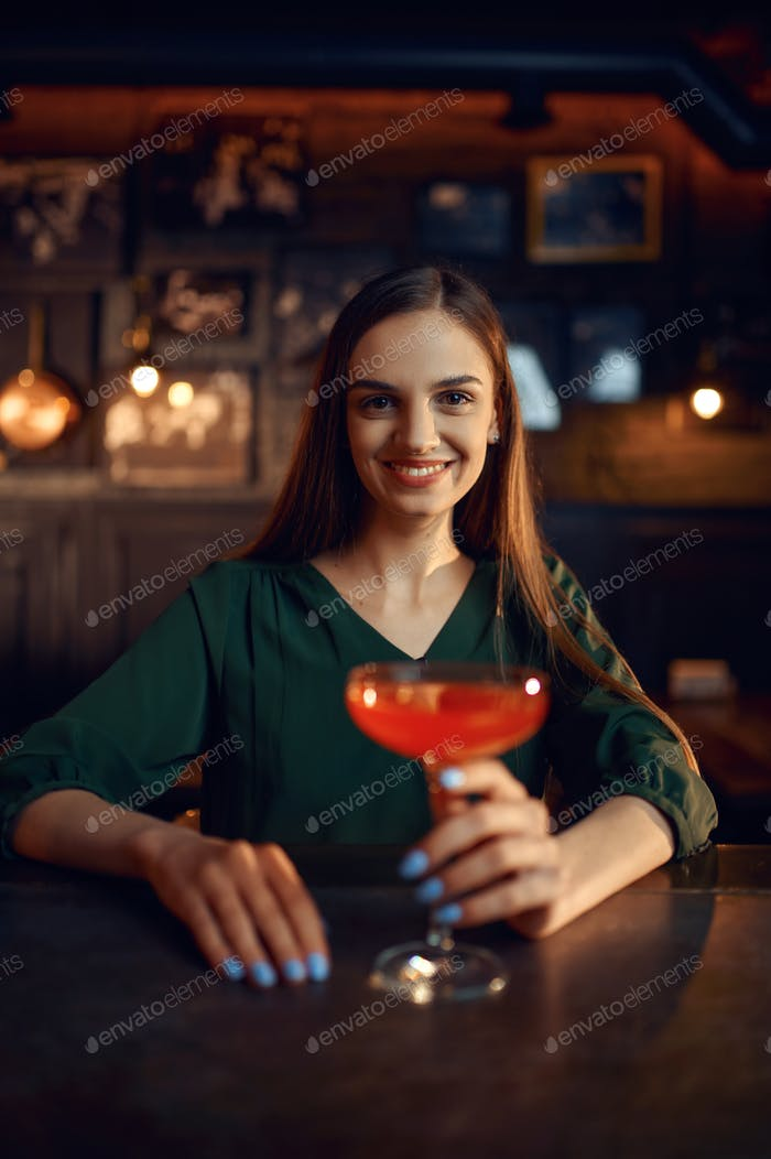 Smiling woman drinks coctail at the counter in bar