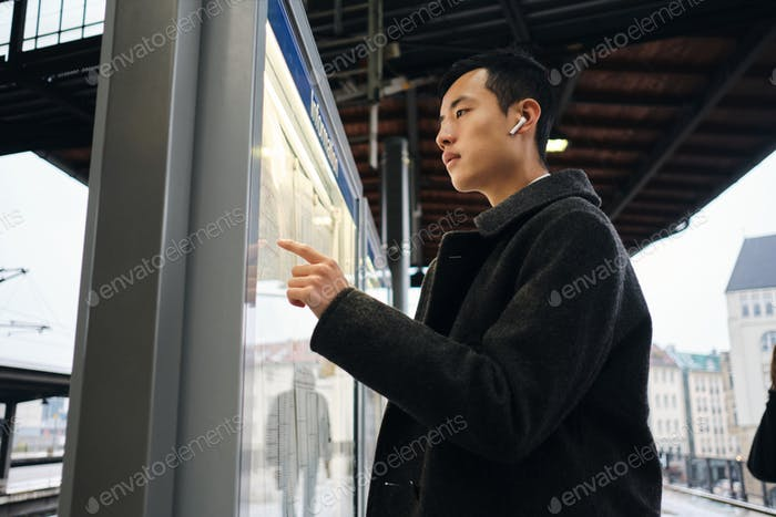 Asian businessman thoughtfully watching timetable of public transport at metro station