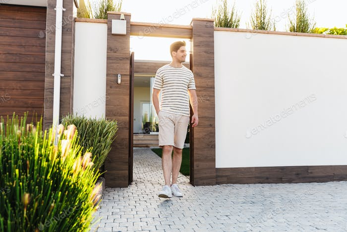 Positive woman standing near home gate outdoors.