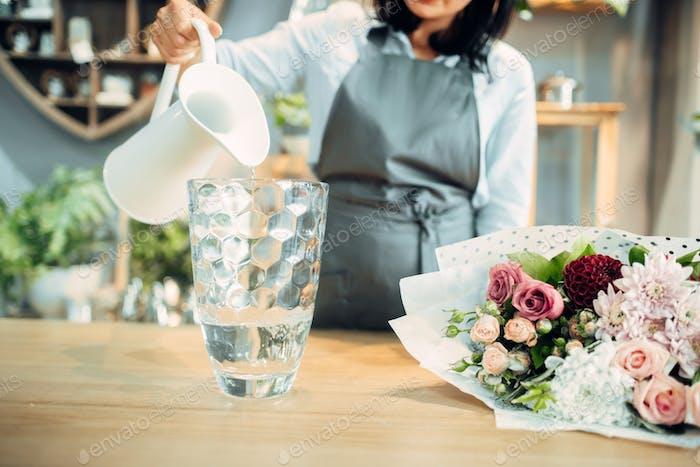Florist pours water into a vase in flower shop