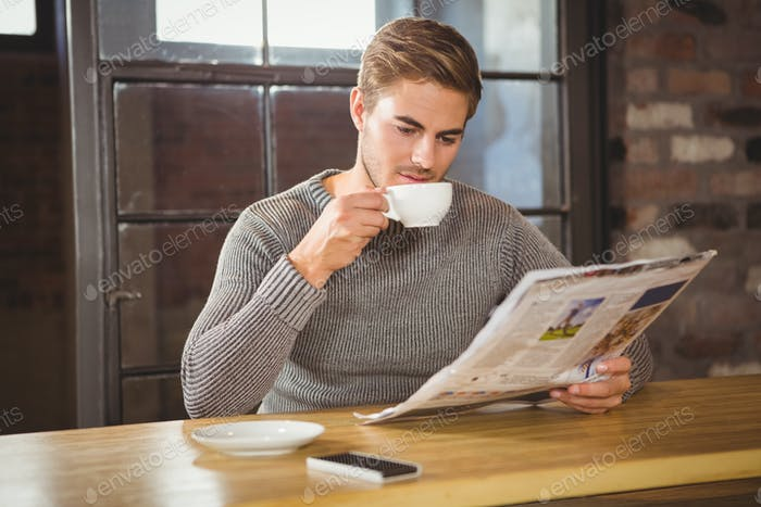 Handsome man drinking coffee and reading newspaper at coffee shop