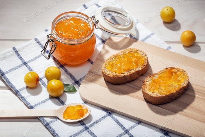 Topf mit hausgemachter süßer Marmelade und Toast auf Holztisch