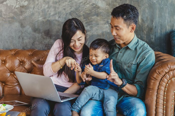 Asian family with son are looking the cartoon via technology laptop and playing together
