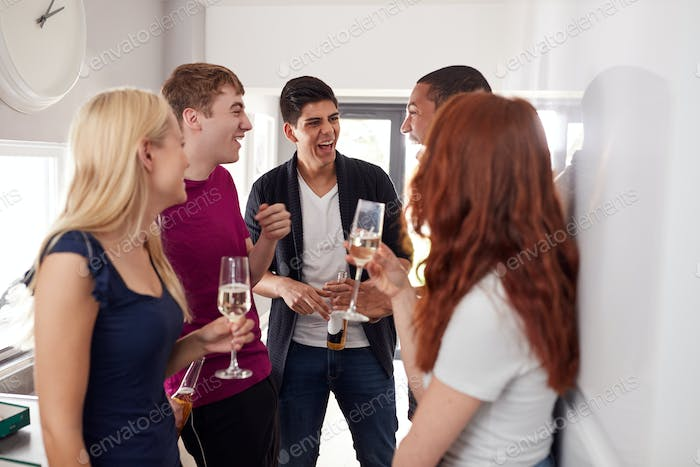 Group Of College Students In Shared House Kitchen Hanging Out And Drinking Together
