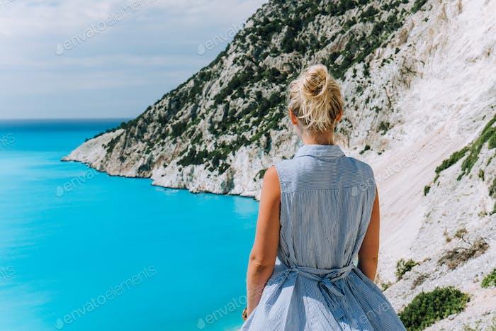 Women tourist enjoying Myrtos Beach. Travel vocation concept. Kefalonia, Ionian Sea, Greece