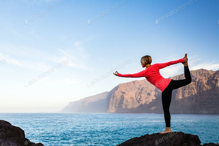 Woman meditating in yoga dancer pose, inspiring landscape