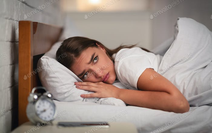 Young Woman Suffering From Insomnia Lying In Bed At Home