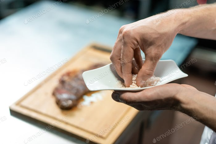Hands of chef taking marine salt from plate to add it to roasted beef steak