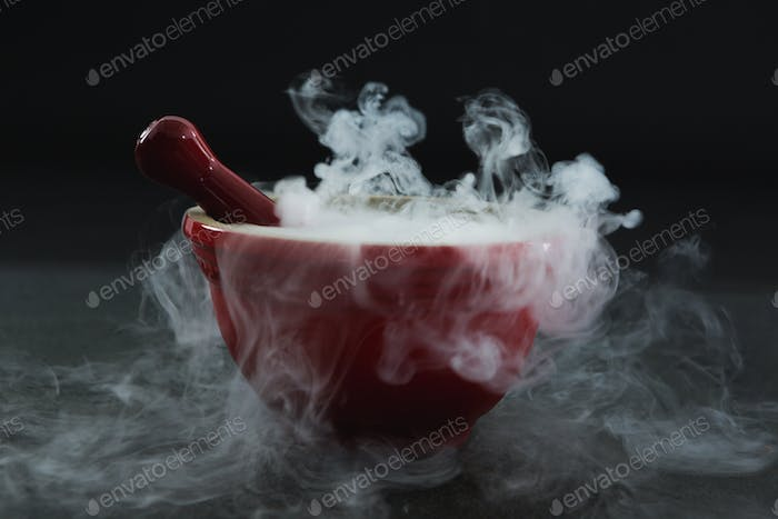 Dry ice smoke in bowl on black background
