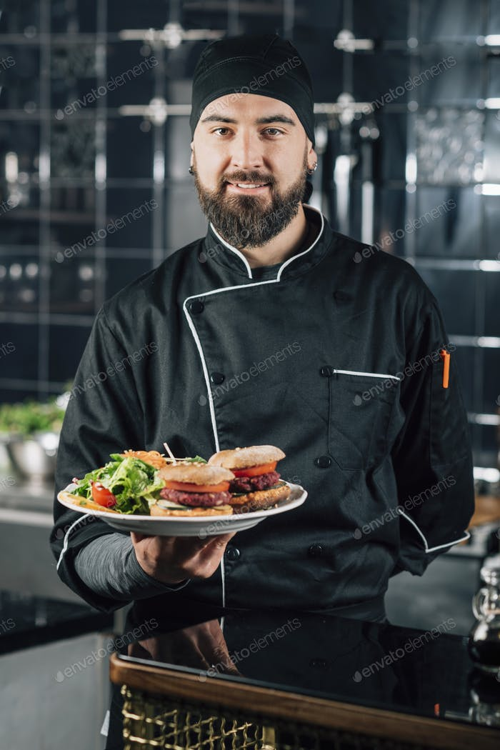Smiling Male Restaurant Chef, Holding a Plate with Vegetarian Meal