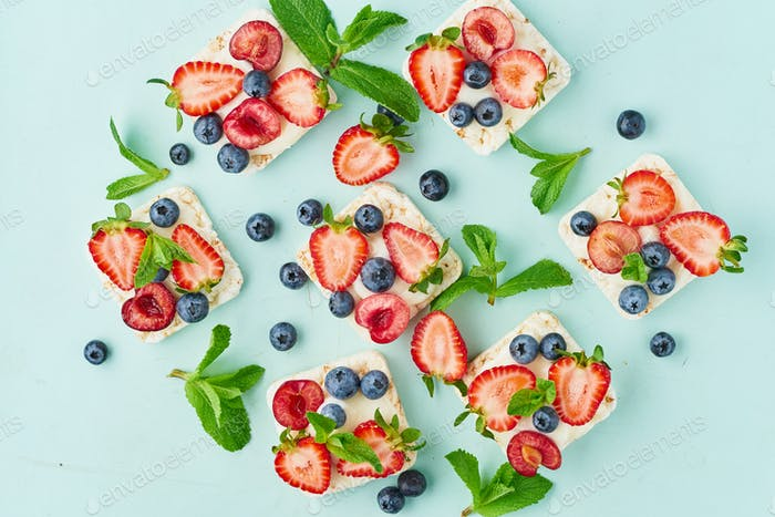 Rice crispbread with berries and fruits colorful concept on turquoise aquamarine background