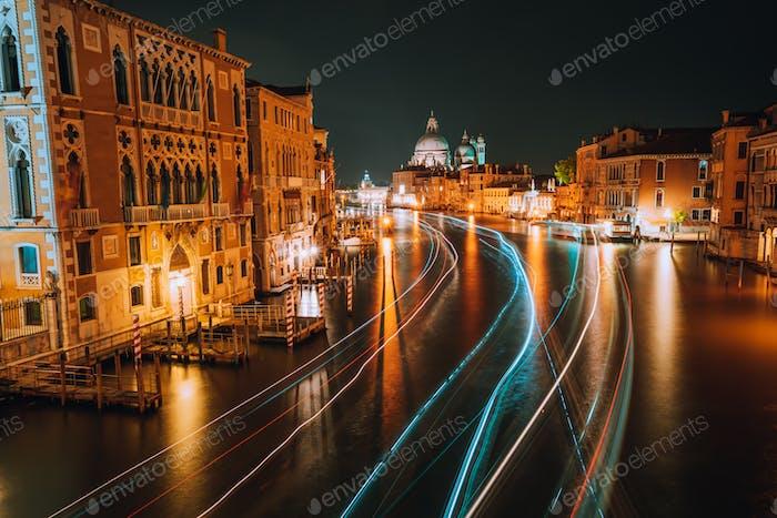 Venedig Dämmerung blaue Nacht Landschaft. Licht beleuchtete Wege von Fähren und Booten reflektiert auf der