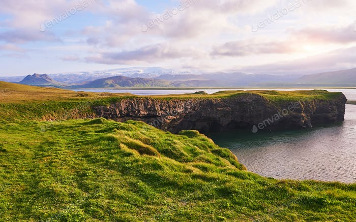 Cape Dyrholaey at southern Iceland. Altitude 120 m, and mean hill island with a door opening