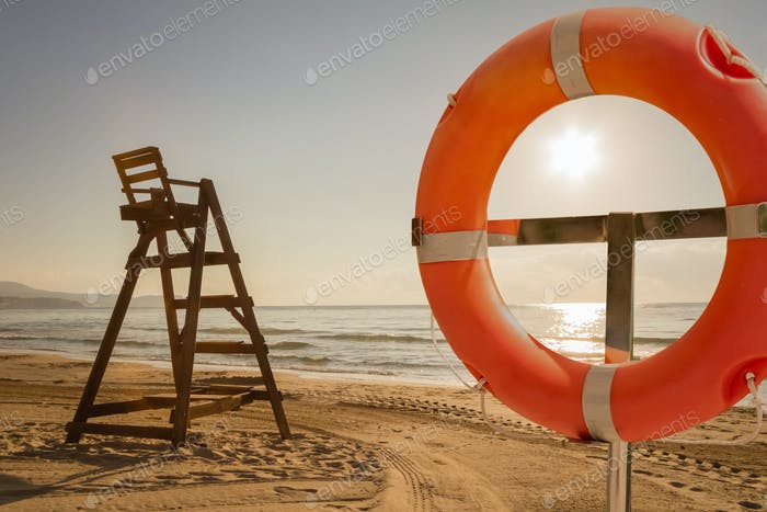 Baywatch chair and life ring in a beach at sunset