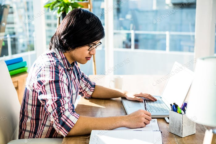 Hipster businessman writing while using laptop in office