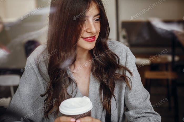 Gorgeous young woman with cup of coffee sitting in cafe and looking through window