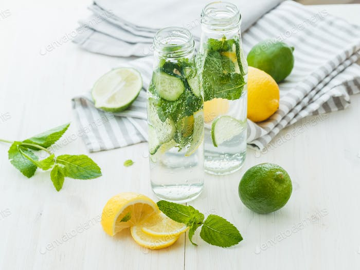 Infused water with citrus and mint in glass bottles on wooden ba