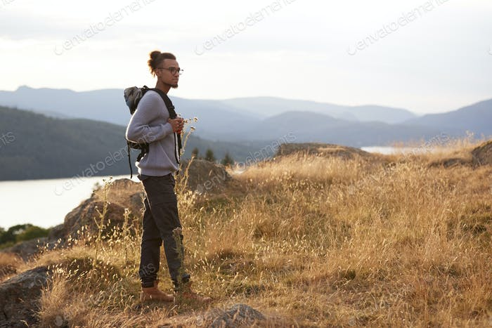 A young mixed race man standing alone on a hill