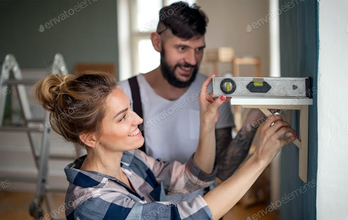 Mid adults couple with leveler indoors at home, relocation and diy concept