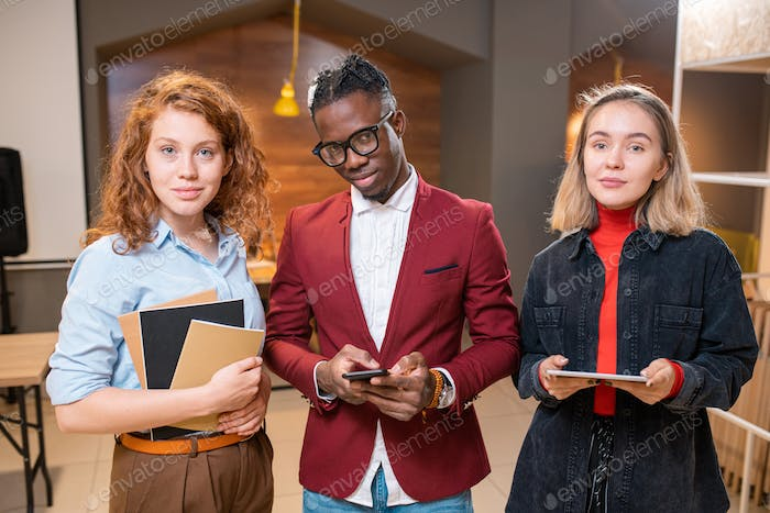 Row of three successful contemporary multicultural students of university
