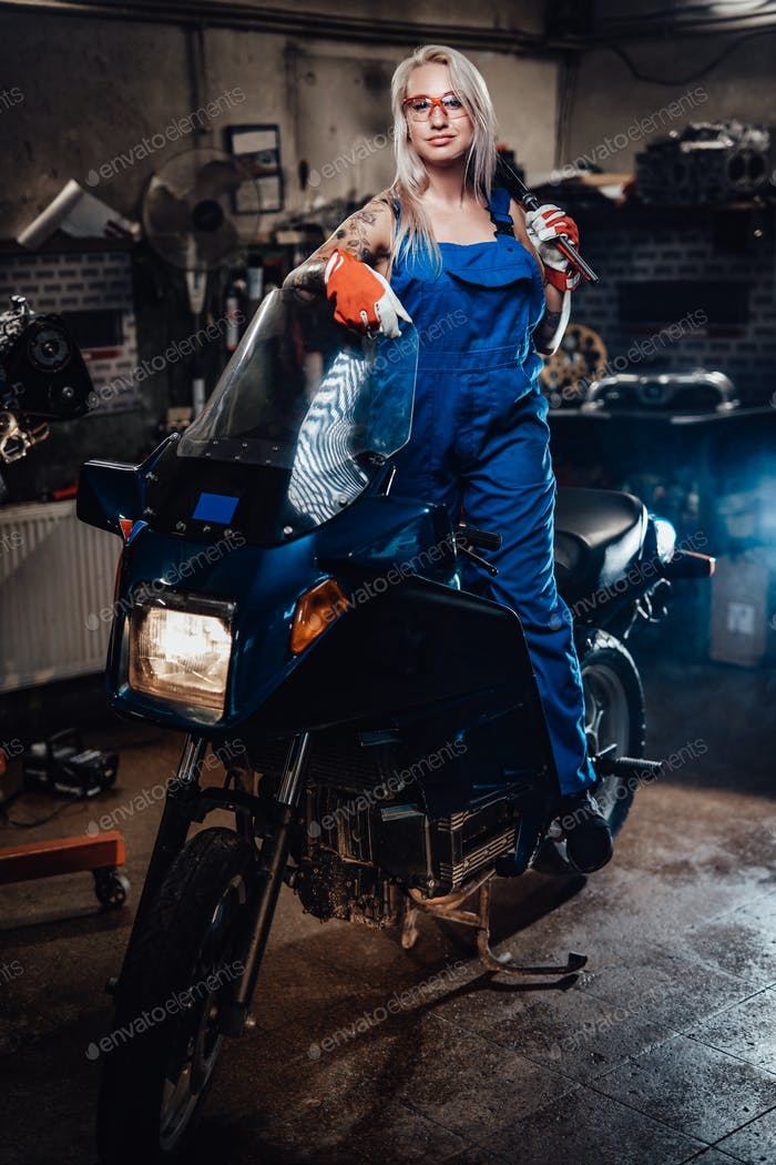 Blond female mechanic with tattooed hands wearing work overalls posing on her sportbike in garage