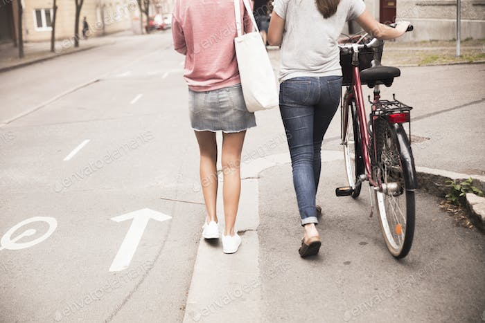 Young women walking with bike
