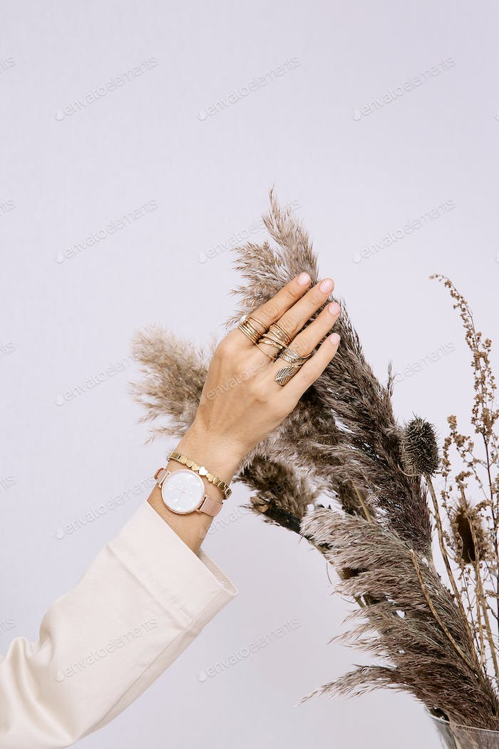 Fashion Accessories. Watches & Rings Ladies hand and flowers decor. Minimal style in details concept