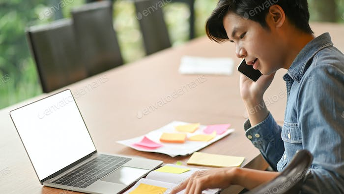 Young business men are calling to work and use laptop.