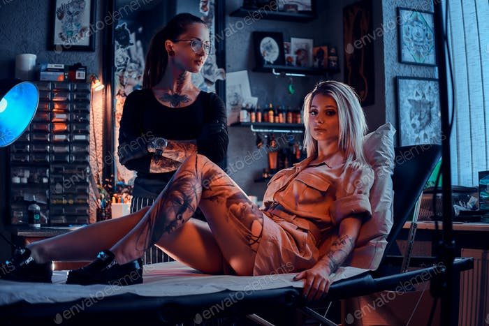 Two beautiful girls at tattoo studio