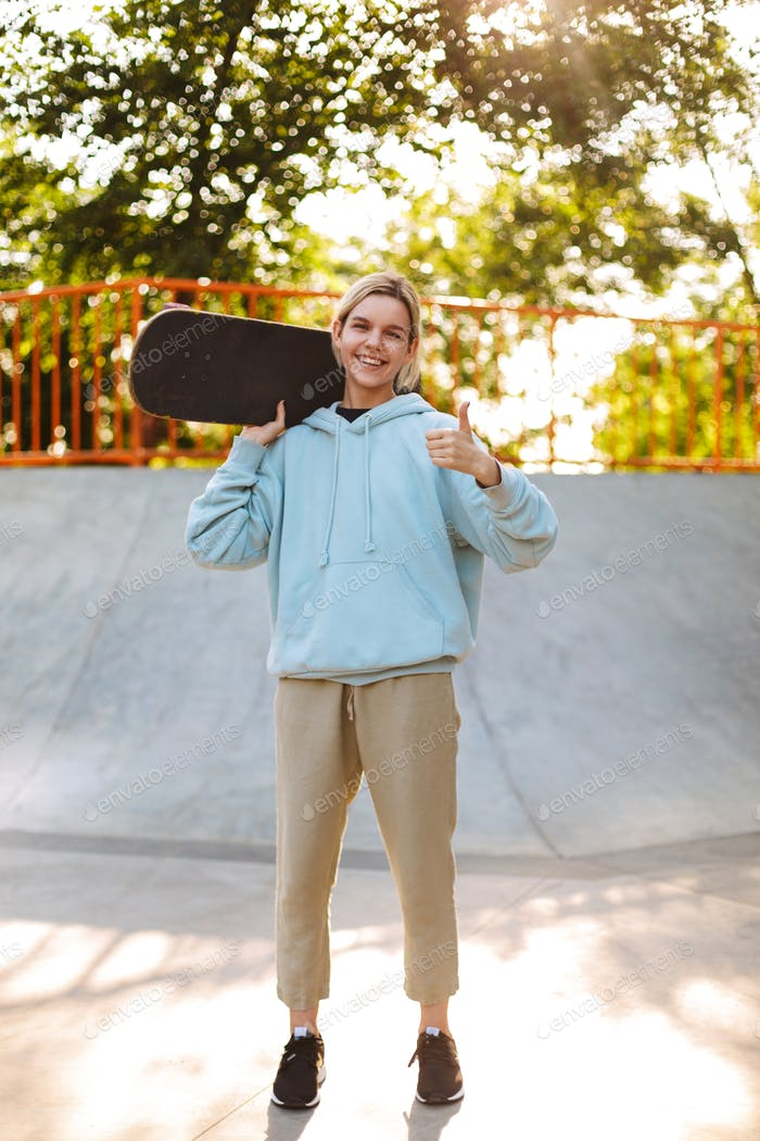 Beautiful smiling girl in hoodie holding skateboard on shoulder