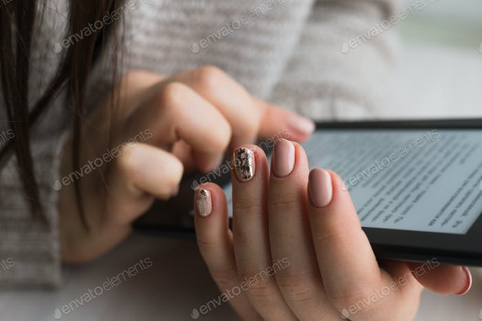 Junge Frau sitzt am Fenster mit einem E-Book