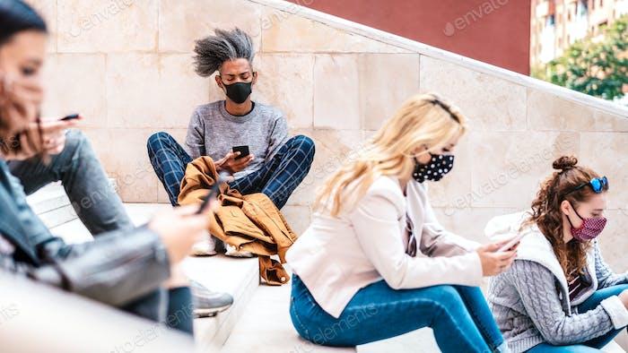 Städtische Millennials nutzen Smartphones mit Gesichtsmaske auf der dritten Welle von Covid