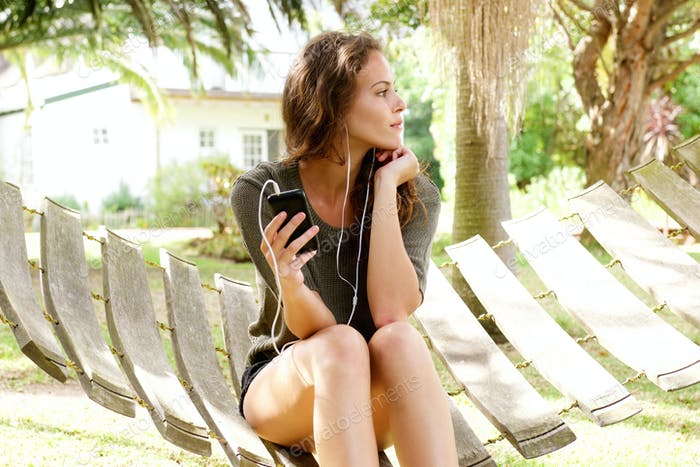 Young woman sitting in backyard listening to music