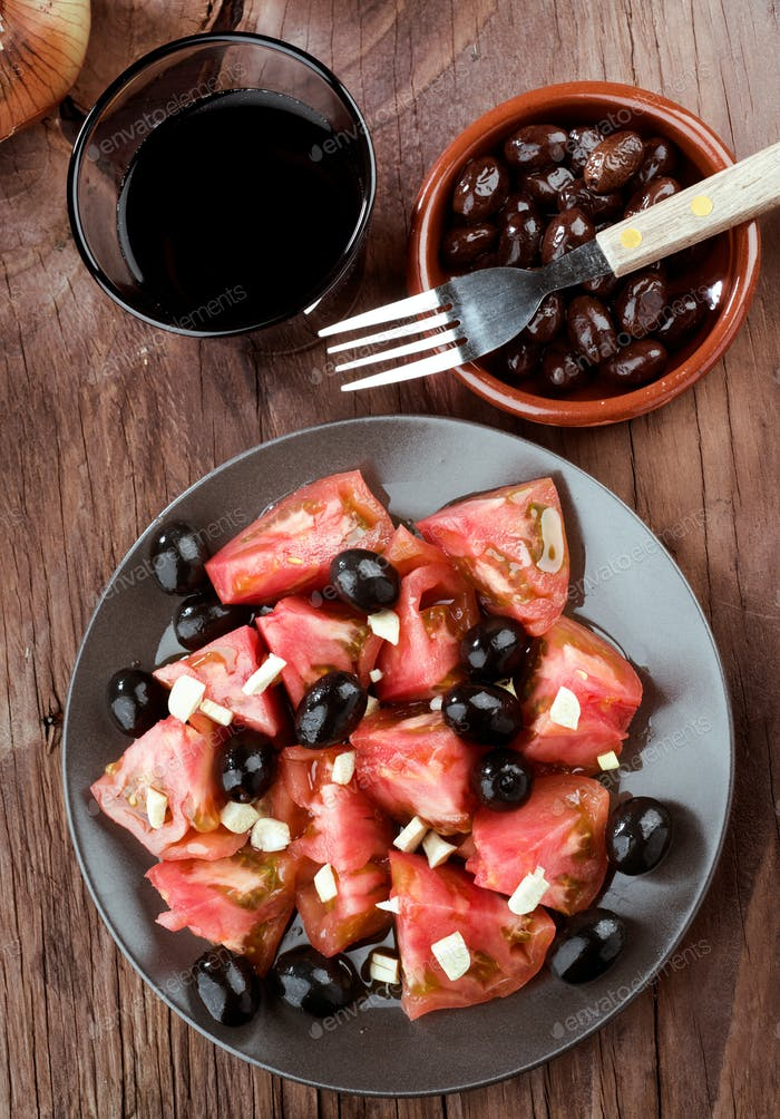 tomato salad and black olives on rustic wooden board