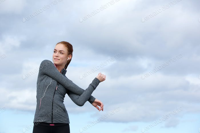 Young woman stretching body muscles