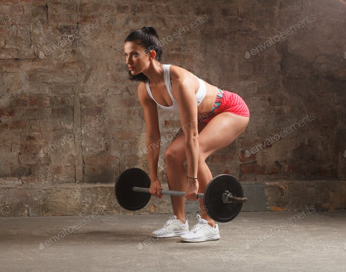 sportswoman doing dead lift exercise with barbell
