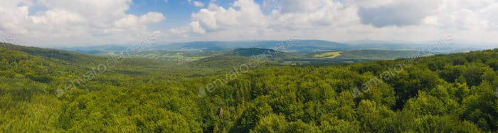 Vast summer scenery with green forested hills from aerial perspective