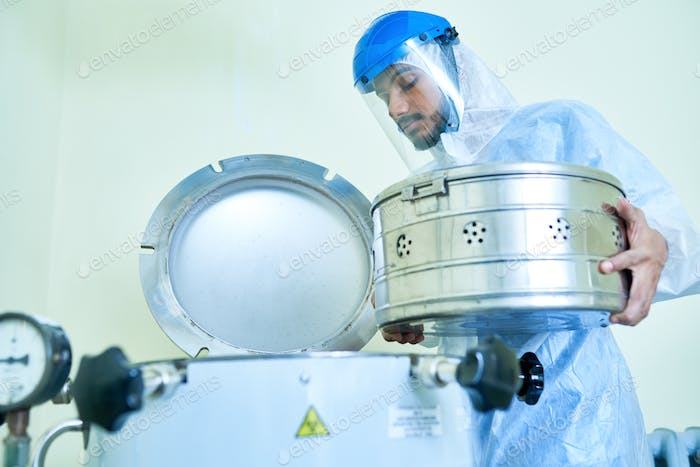 Laboratory assistant putting container into centrifuge