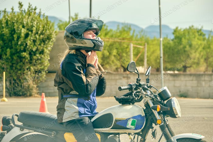 Woman sitting on motorcycle and taking off helmet