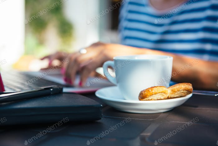 Coffee with cookie at working woman