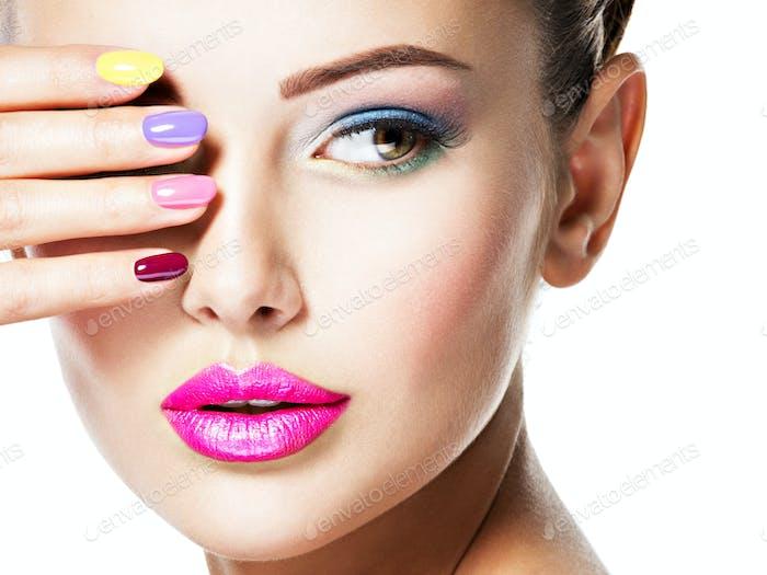 schöne Frau mit mehrfarbigen Nägeln und Mode Make-up