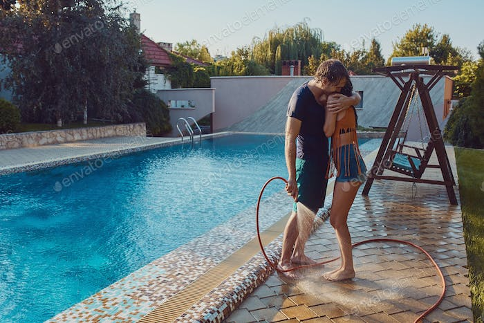 Couple having fun pour each other with garden hose